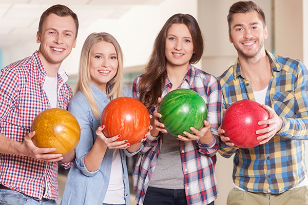 Pretty young men and women are playing bowling together. They are standing and holding the ball. The players are smiling and looking at camera happily