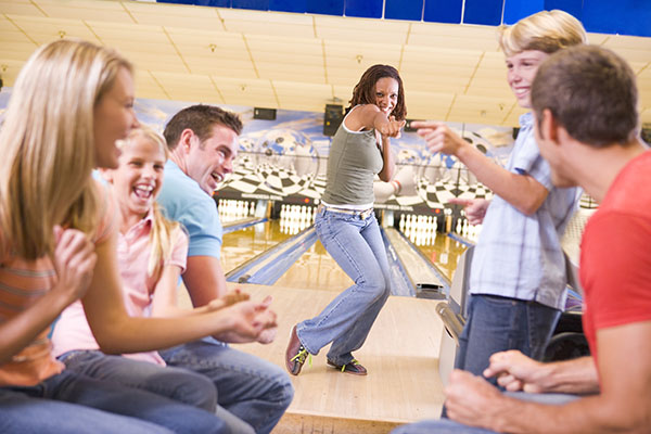 Families Having Fun At Bowling Alley