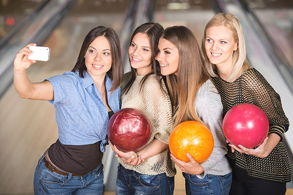 A Group Of Young Female Friends Are Taking A Self Portrait With A Phone In Bowling Club.